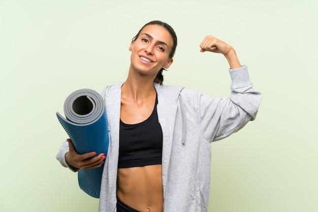 Junge sportfrau mit matte über lokalisierter grüner wand