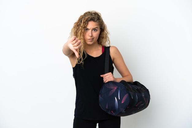 Junge sportfrau mit sporttasche isoliert auf weißem hintergrund mit daumen nach unten mit negativem ausdruck