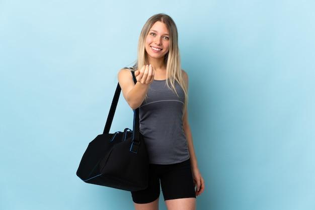 Junge sportfrau mit sporttasche lokalisiert auf blau einladend, mit hand zu kommen. schön, dass du gekommen bist