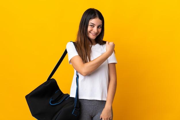 Junge sportfrau mit sporttasche lokalisiert auf gelb, die einen sieg feiert