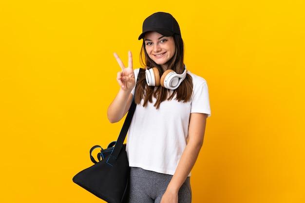 Junge sportfrau mit sporttasche lokalisiert auf gelbem lächeln und siegeszeichen zeigend