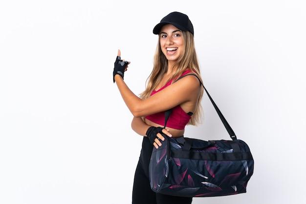 Junge sportfrau mit sporttasche über isoliertem weißem hintergrund, der nach hinten zeigt