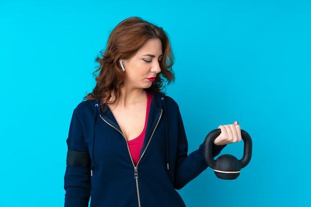 Junge sportfrau über dem lokalisierten blauen hintergrund, der das gewichtheben mit kettlebell macht