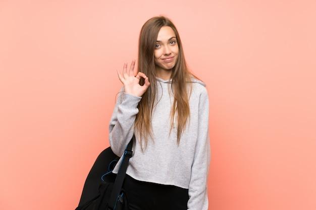 Junge sportfrau über dem lokalisierten rosa, das ein okayzeichen mit den fingern zeigt