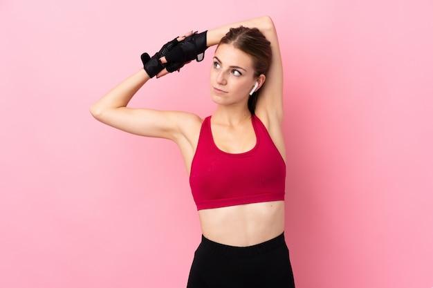 Junge sportfrau über dem lokalisierten rosa wandausdehnen