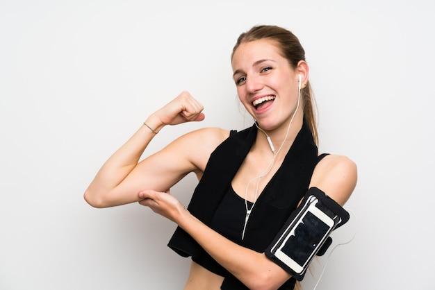 Junge sportfrau über dem lokalisierten weiß, das starke geste macht