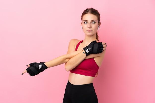 Junge sportfrau über der lokalisierten rosa wand, die arm ausdehnt