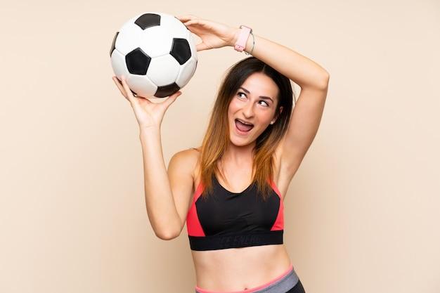 Junge sportfrau über der lokalisierten wand, die einen fußball hält