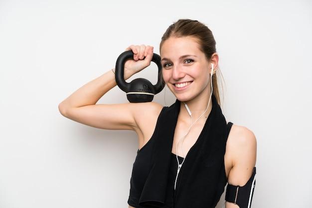 Junge sportfrau über der lokalisierten weißen wand, die das gewichtheben mit kettlebell macht