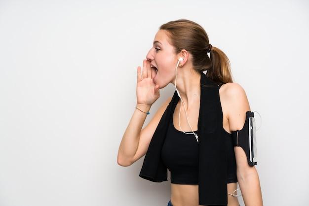 Junge sportfrau über der lokalisierten weißen wand, die mit dem breiten mund schreit, öffnen sich