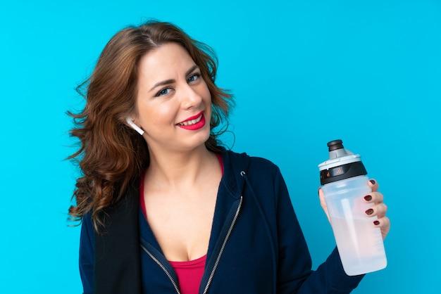 Junge sportfrau über getrenntem blau mit sportwasserflasche