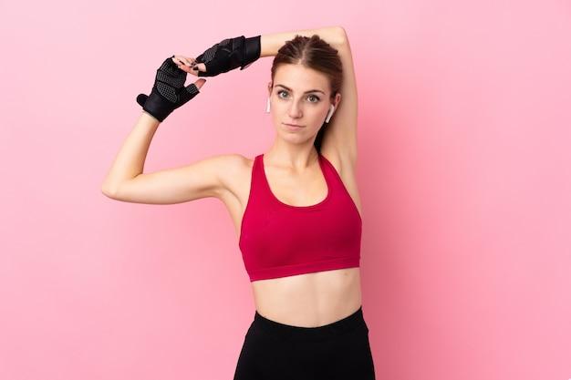 Junge sportfrau über isolierte rosa wanddehnung