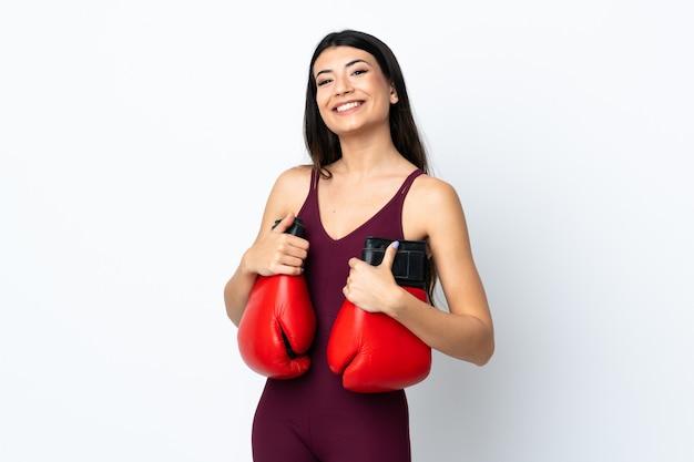 Junge sportfrau über isolierter weißer wand mit boxhandschuhen