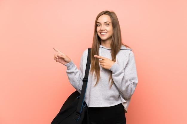 Junge sportfrau über lokalisiertem rosa hintergrund finger auf die seite zeigend