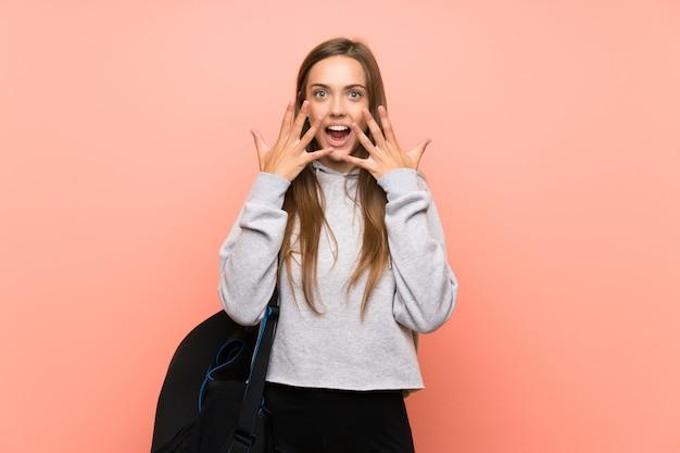 Junge sportfrau über lokalisiertem rosa hintergrund mit überraschungsgesichtsausdruck