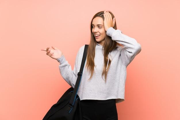 Junge sportfrau über lokalisiertem rosa überraschte und finger auf die seite zeigend