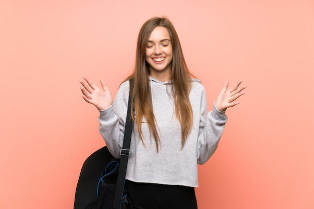Junge sportfrau über lokalisiertem rosa wandlachen