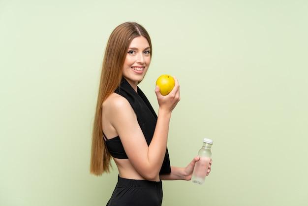 Junge sportfrau über lokalisierter grüner wand mit einem apfel
