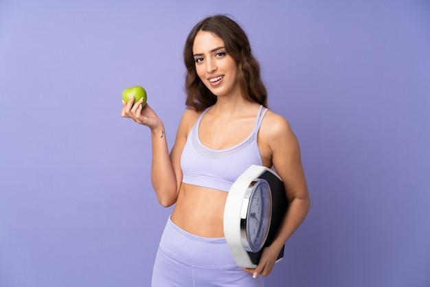 Junge sportfrau über lokalisierter purpurroter wand mit waage und mit einem apfel