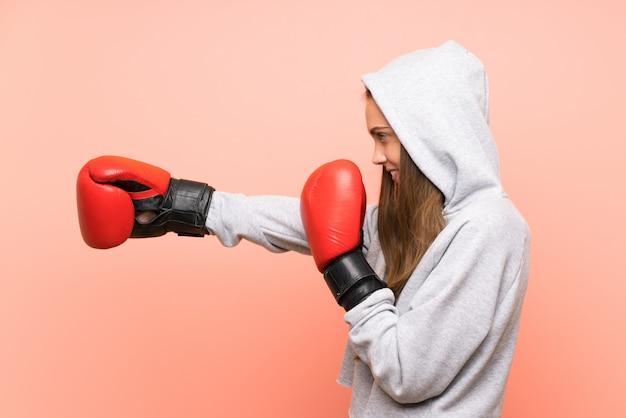Junge sportfrau über lokalisierter rosa wand mit boxhandschuhen