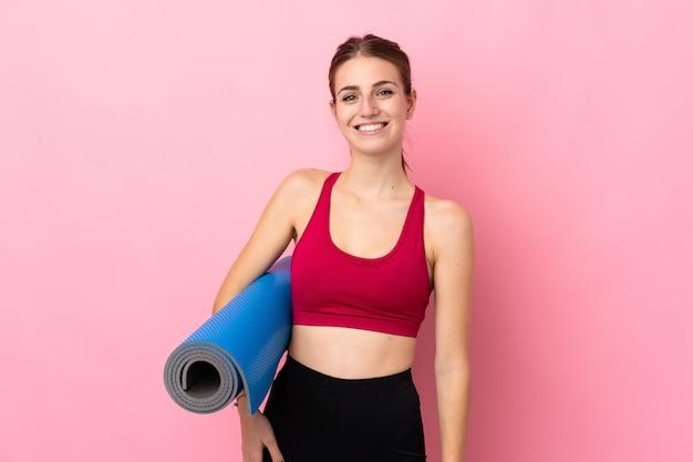 Junge sportfrau über lokalisierter rosa wand mit einer matte und einem lächeln
