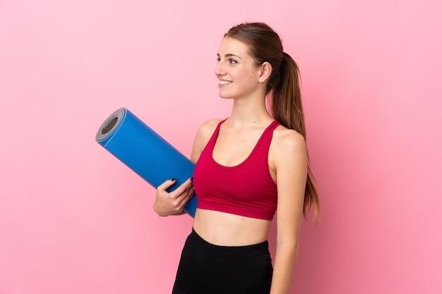 Junge sportfrau über lokalisierter rosa wand mit einer matte