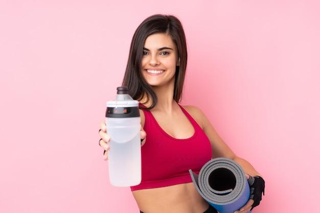 Junge sportfrau über lokalisierter rosa wand mit sportwasserflasche und mit einer matte