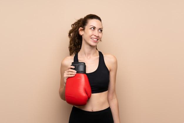 Junge sportfrau über lokalisierter wand mit boxhandschuhen