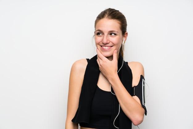 Junge sportfrau über lokalisierter weißer wand eine idee denkend