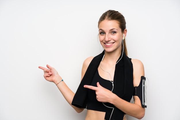 Junge sportfrau über lokalisierter weißer wand finger auf die seite zeigend