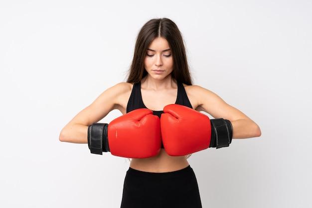 Junge sportfrau über lokalisierter weißer wand mit boxhandschuhen