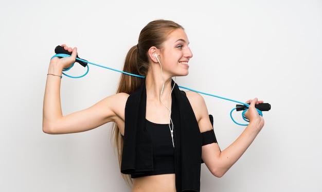 Junge sportfrau über lokalisierter weißer wand mit springendem seil