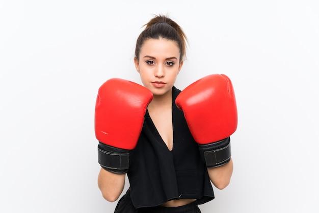 Junge sportfrau über weißer wand mit boxhandschuhen