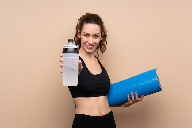 Junge sportfrau vorbei lokalisiert mit sportwasserflasche und mit einer matte