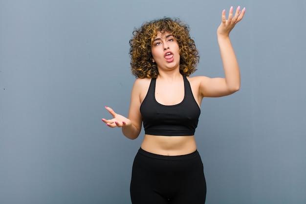 Junge sportfrau zuckt die achseln mit einem dummen, verrückten, verwirrten, verwirrten ausdruck, der sich auf der grauen wand genervt und ahnungslos fühlt