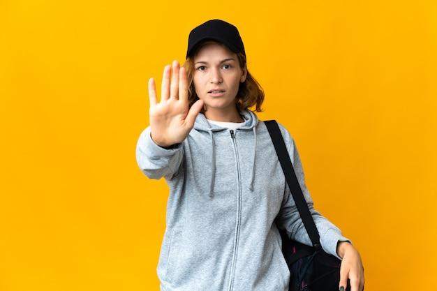 Junge sportgeorgianerin mit sporttasche über isolierter wand, die stoppgeste macht