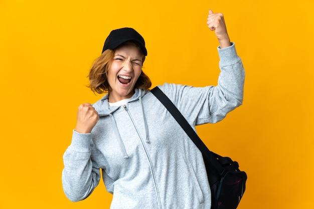 Junge sportgeorgianerin mit sporttasche über lokalisiertem hintergrund, der einen sieg feiert