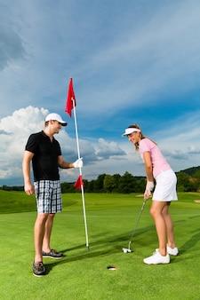 Junge sportive paare, die golf auf einem kurs spielen