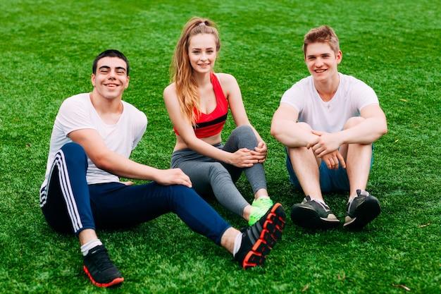 Junge sportler sitzen auf dem rasen