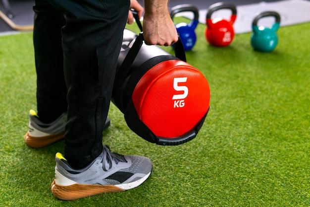 Junge sportlerhände halten und heben einen gewichtsrucksack