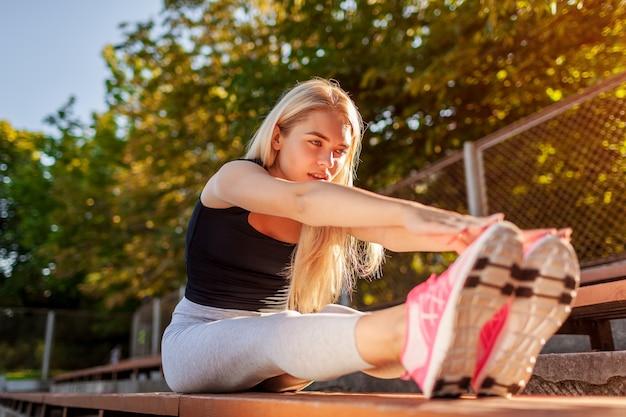 Junge sportlerin, die sich aufwärmt, bevor sie im sommer auf dem sportplatz läuft. körper dehnen. morgengymnastik machen