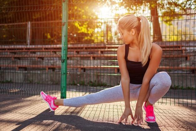 Junge sportlerin, die sich aufwärmt, bevor sie im sommer auf dem sportplatz läuft. sportlicher weiblicher stretching-körper. aktiver lebensstil