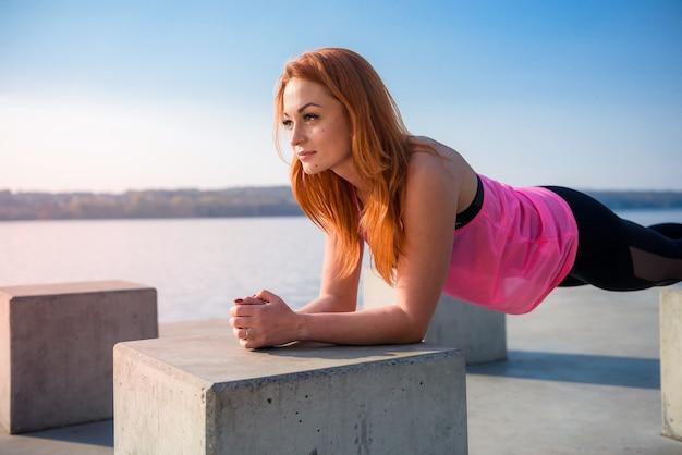 Junge sportlerin, die tagsüber liegestütze im freien in der nähe des sees macht. gesunder lebensstil
