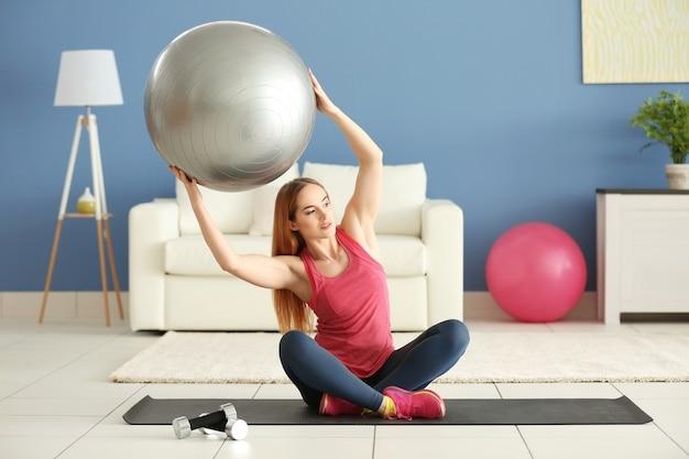 Junge sportlerin, die übungen mit ball auf einer matte zu hause macht