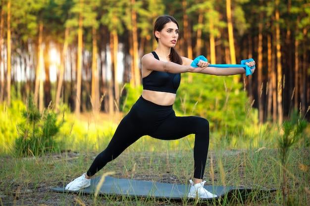 Junge sportlerin führt eine gymnastikübung in der natur durch