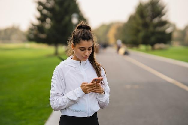 Junge sportlerin hält und benutzt smartphone nach dem joggen