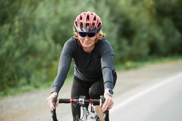 Junge sportlerin im helm, die mit ihrem fahrrad auf einer straße im grünen fährt