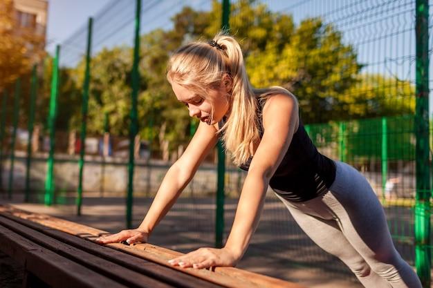 Junge sportlerin macht im sommer liegestütze auf dem sportplatz. gesunder lebensstil. motivation