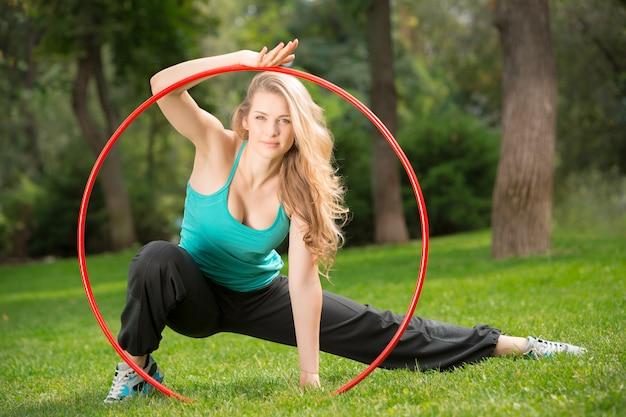 Junge sportlerin mit hula hoop im park