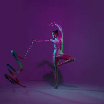 Junge sportlerin, rhythmische gymnastikkünstlerin tanzt, trainiert lokalisiert auf lila studiahintergrund mit neonlicht. schönes mädchen, das mit ausrüstung übt. anmut in der leistung.